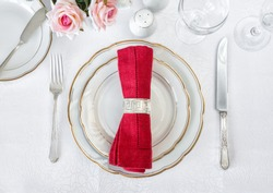 Beautifully decorated table with white plates, glasses, antique cutlery and red napkin are on luxurious tablecloths