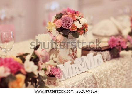 Beautifully decorated wedding table with flowers and MR&MRS letters