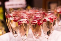Beautifully decorated welcome drink - a glass of Prosecco or champagne with raspberry inside, served as a welcome drink on a party, event, wedding reception or banquet.
