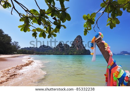 Beautifully decorated with colored silks Native boat Longtail on a sandy beach in Thailand