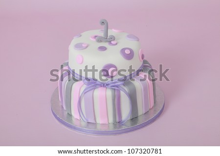 Beautifully designed and decorated girls double tier round birthday party cake with white fondant icing and purple and pink stripes and circular polka dots with number one isolated on pink background