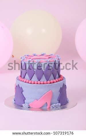Beautifully designed and decorated two double tier princess themed birthday cake with purple and pink butter and fondant icing featuring beads shoes crown and diamonds on pink background with balloons