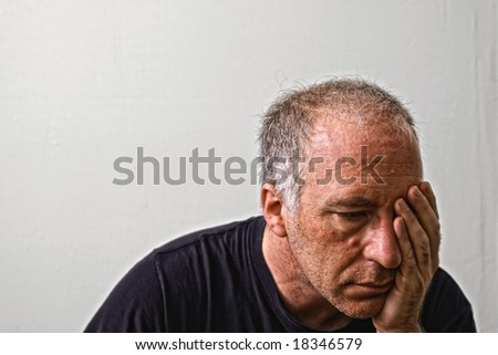 beautifully detailed real portrait of haggared looking adult white man holding his head as if having a headache or is in deep dispair