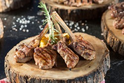 Beautifully grilled lamb rib chop steaks, medium rare with fried potato chips on wood serving board.