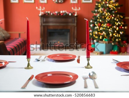 Beautifully laid new year table with red plates and Cutlery on a background of decorated room with Christmas tree and fireplace