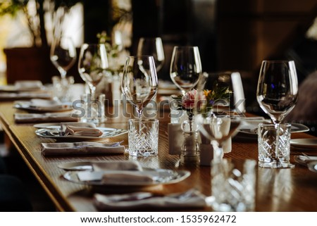 beautifully laid tables with glasses and appliances at morning in restaurant