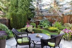 Beautifully landscaped small Canadian garden in summer. Blue spruces, hosta, astilbes and azaleas are just some of the many plants in this cozy little backyard.
