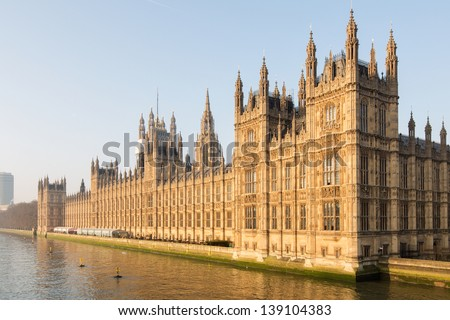 beautifully lit by the early morning sun at dawn, the British Parliament westminster at full glory on the side of river Thames in London, UK