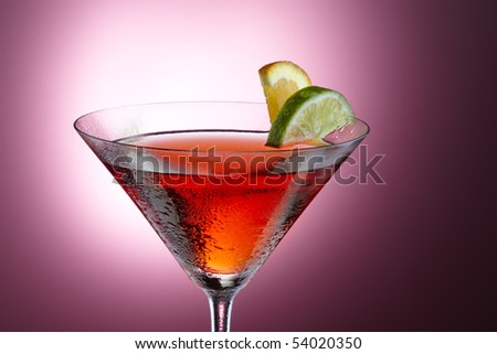 Beautifully lit Cosmopolitan with slices of lemon and lime shot on pink background, space for copy