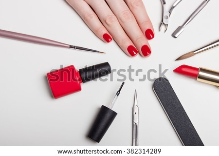 beautifully manicured nails on the desktop with tools for manicure