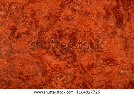 Beautifully patterned wood burl veneer with a brown and red swirling look.