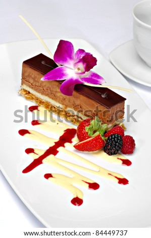 Beautifully plated chocolate mousse cake garnished with a purple orchid, strawberry, blackberry and raspberry.  A zigzag of white chocolate and strawberry sauce completes the plate.