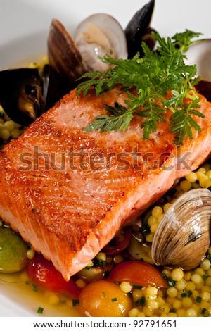 Beautifully plated salmon fillet garnished with colorful green parsley.  Served over a couscous and seafood salad featuring mussels, clams, tomatoes and brussels sprouts.
