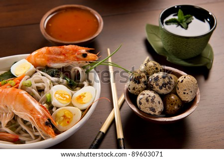 Beautifully prepared prawns and quail eggs served over noodles. Chopsticks, a bowl with sauce, a tea cup and a bowl of quail eggs are also on the table.