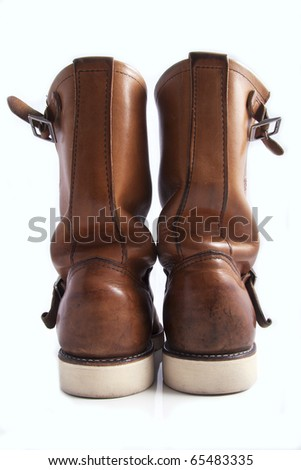 beautifully worn dark brown all american fashion boots seen from the back isolated on white