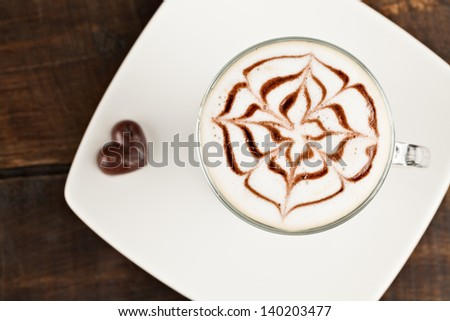 Beautifuly decorated cup of cafe latte and chocolate heart, against polished table top