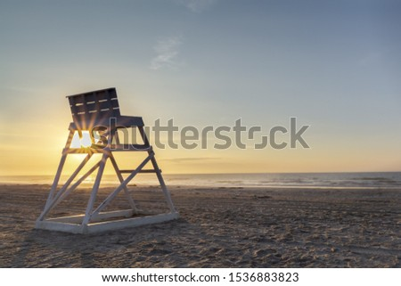 Beautify sunrise on the New Jersey shore, fingers of sunlight reach through a lifeguard chair at dawn. Tranquil morning