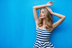 beautty fashion portrait of blonde woman with red lips and stripped dress. Fashion portrait. Smiling blonde woman in fashionable look. Sea style. On blue background. Style and hot girl outdoor.