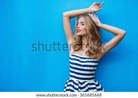 Stock Photo beautty fashion portrait of blonde woman with red lips and stripped dress. Fashion portrait. Smiling blonde woman in fashionable look. Sea style. On blue background. Style and hot girl outdoor.