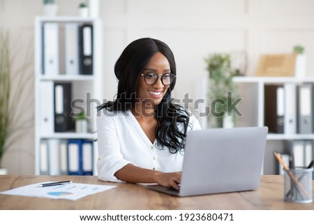 Beautuful black businesswoman working with laptop computer at desk in office. African American female entrepreneur typing document, checking email, participating in online meeting at workplace