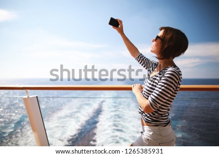 beauty adult brunette woman with hairstyle taking pictures with her smartphone from the deck on cruise liner ship.Travel concept.