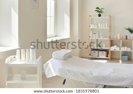 Beauty and body care. Interior of new beauty salon with spa massage table and set of skincare products ready for use. Empty professional dermatologist room waiting for customers ストックフォト ©