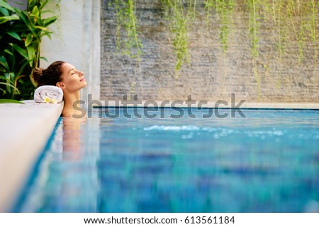 Beauty and body care. Sensual young woman relaxing in outdoor spa swimming pool. #613561184