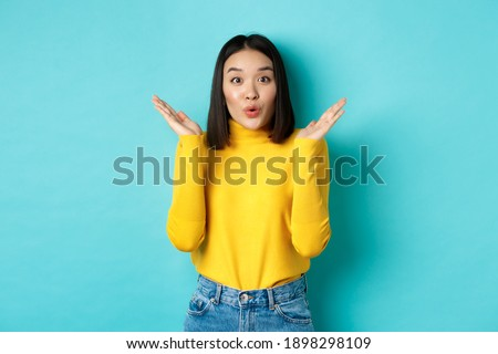 Beauty and fashion concept. Image of excited and surprised japanese girl saying wow with amazement, raising hands up near face, standing against blue background Photo stock ©