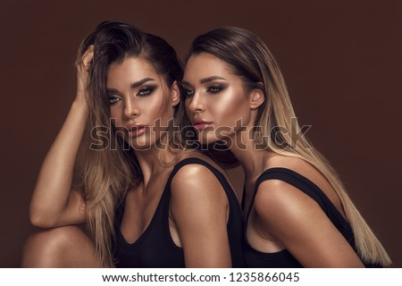 Beauty and femininity concept. Two attractive twins women in glamour makeup. Portrait photo.