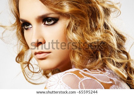 Beauty and health, cosmetics and make-up. Close-up portrait of beautiful woman model with long curly shiny hair, lace on shoulders, dark evening make-up. - stock photo