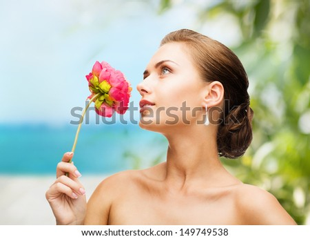 beauty and jewelry concept - woman wearing earrings and smelling flower
