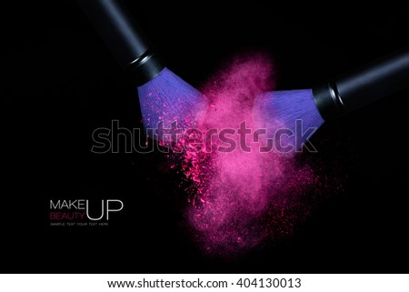 Beauty and Makeup concept. Stop action view of two makeup brushes applying matching neon pink powder over black background. Colorful dust explosion