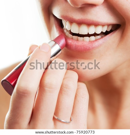 Beauty and makeup concept. Woman applying red lipstick on lips