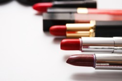 Beauty and makeup cosmetics. Flat lay of lipsticks and color gloss isolated on white background, shallow depth of field, close-up, copy space