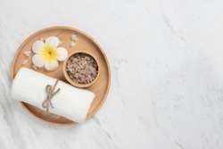 Beauty and Massage composition, Top view of Thai Spa products on wooden tray in round shape on white marble background. Towel, Salt, Plumerias  Flower, Copy space.