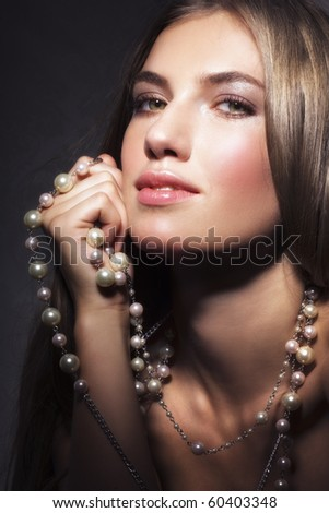 Beauty and pearl necklace on dark background