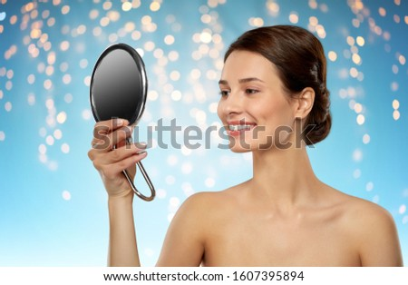 beauty and people concept - beautiful young woman with bare shoulders looking to mirror over holidays lights on blue background