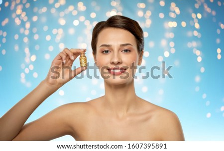 beauty and people concept - beautiful young woman with gold facial mask in bottle over holidays lights on blue background