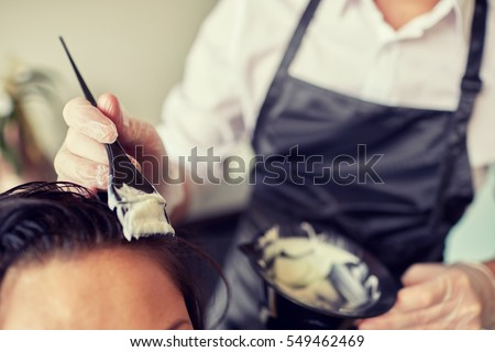 beauty and people concept - close up of stylist with hair dye and brush coloring hair at salon #549462469