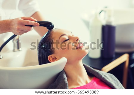 beauty and people concept - happy young woman with hairdresser washing head at hair salon #565493389