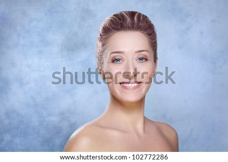 Beauty and skin care concept / Beautiful smiling brunette woman with blue eyes