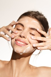 Beauty and skin care concept. Topless woman smiling while cleaning her face with nourishing cleansing foam with hyaluronic acid, close eyes, rubbing cheeks for deep hydration, white background.