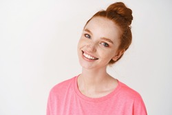 Beauty and skincare. Close-up of young redhead woman with freckles and blue eyes touching clean, no make-up skin and smiling, standing in pink t-shirt against white background.