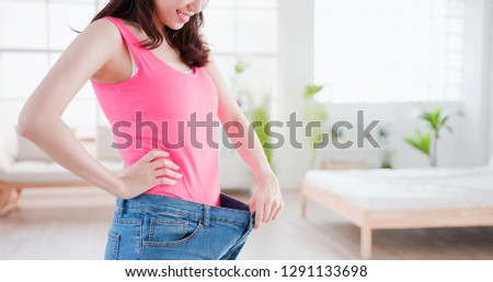 beauty asian woman show loose jeans with weight loss concept