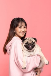Beauty Asian young woman holding dog pug breed on her arm smile and happiness,Owner hug her cute pet dog with love on pink background,Young girl with adorable dog purebred pug breed looking on camera