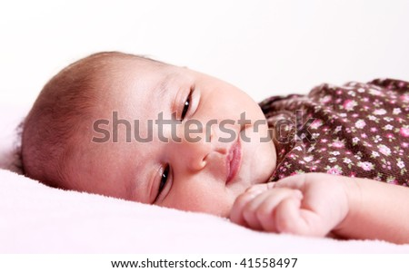Beauty baby dreaming on white blanket.