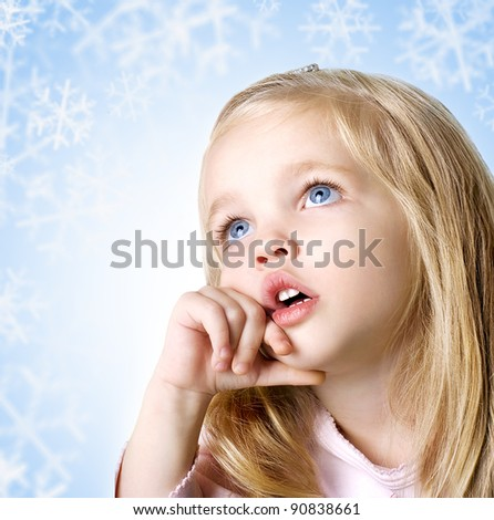 beauty baby face with blue eyes on blue background with snowflakes
