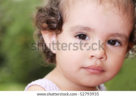 Beauty baby looking at camera over green background. Outdoor image
