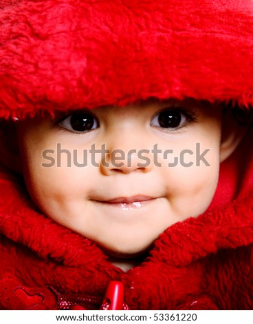 Beauty baby looking at the camera with red hood