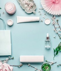 Beauty background with facial cosmetic products, shopping bag and twigs with cherry blossom on pastel blue desktop background. Spring skin care trends, top view, frame, flat lay. Branding mock up